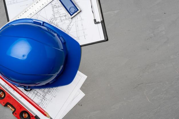 Bouwvakker veiligheidshelm, blauwdrukken en bouwniveau, bovenaanzicht op houten achtergrond