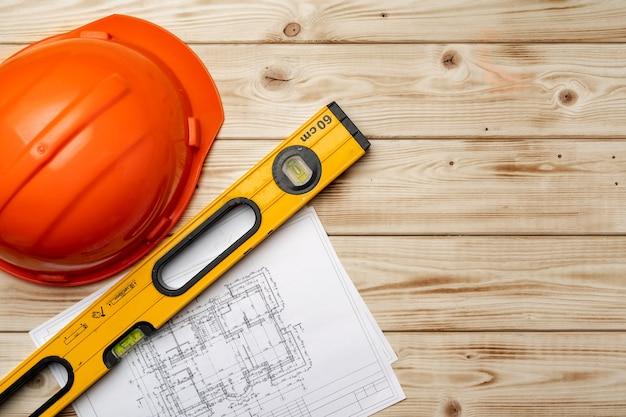 Bouwvakker veiligheidshelm, blauwdrukken en .construction-niveau, bovenaanzicht op houten achtergrond
