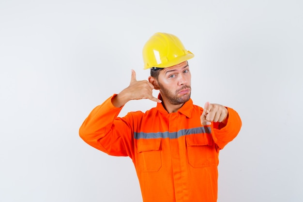 Bouwvakker wijzen met telefoon teken in uniform, helm en op zoek zelfverzekerd. vooraanzicht.
