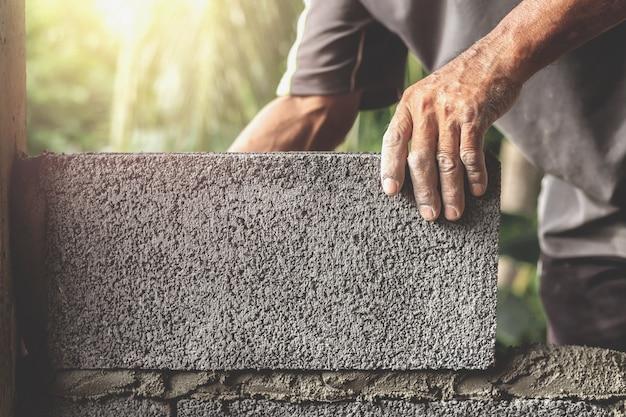 Bouwvakkers bouwen cementmuren met bakstenen blokken.