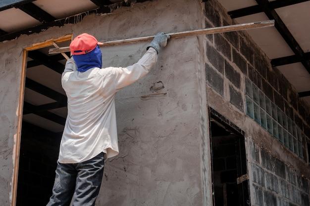 Bouwvakkers die de bouwmuur pleisteren die cementpleister gebruiken