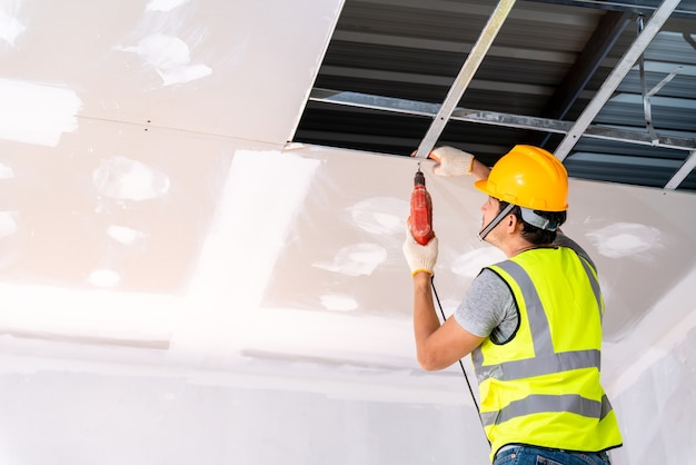 Bouwvakkers die een elektrische boor gebruiken, installeren het plafondhuis in het gebouw in aanbouw, ideeën voor plafondinstallatie ceiling