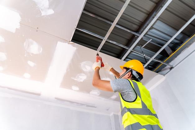 Bouwvakkers die een elektrische boor gebruiken, installeren het plafondhuis op de bouwplaats, ideeën voor plafondinstallatie
