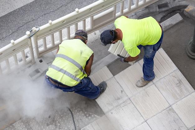 Bouwvakkers die een stoep herstellen. onderhoudsconcept