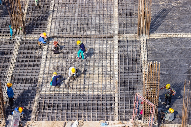 Bouwvakkers die grote stalen staaf maken in het bouwgebied.