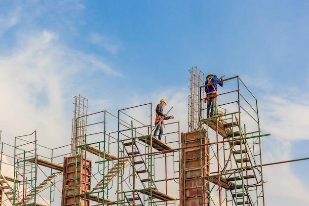 Bouwvakkers die op steiger op een hoog niveau werken