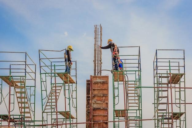 Bouwvakkers die op steigers op hoog niveau werken, hebben een veiligheidsgordel