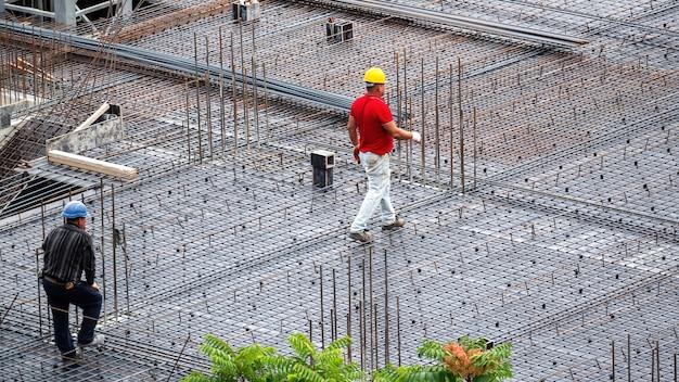 Bouwvakkers die werken op de site in een bewolkte dag