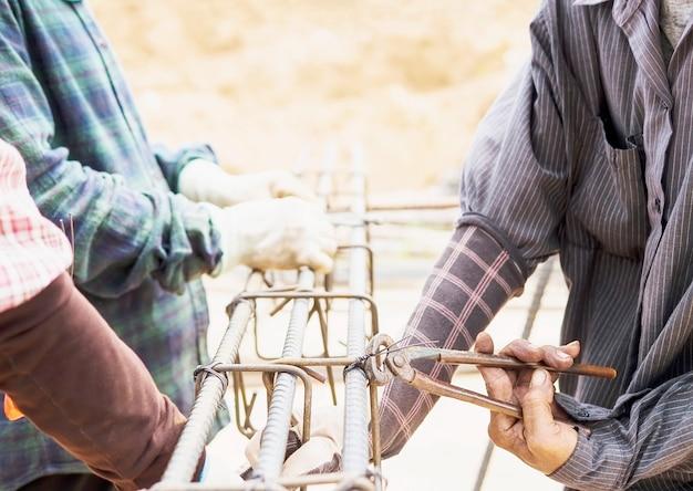 Bouwvakkers installeren stalen staven in een kolom van gewapend beton