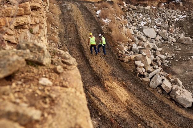 Bouwvakkers lopen in vuil op de site