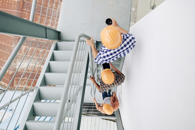 Bouwvakkers met veiligheidshelmen lopen de een na de ander de trap op, uitzicht vanaf de top
