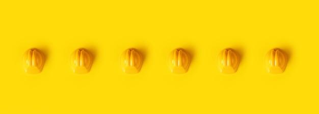 Bouwvakkers over trendy gele achtergrond, panoramisch beeld