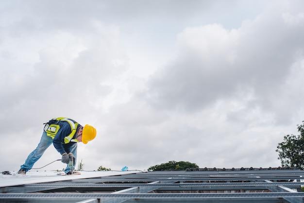 Bouwvakkers zitten op de stalen dakconstructie van het gebouw in het bouwgebied. gebruik een elektrische boor om de moer vast te draaien of installeer het dak van het huis.