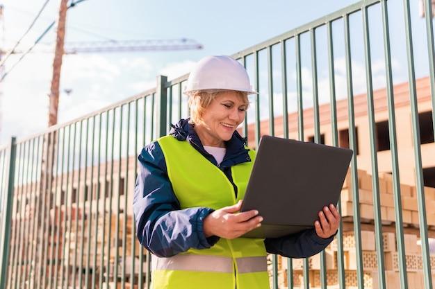 Bouwvakkervrouw op bouwwerf in groen vest en helm met laptop