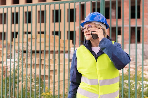 Bouwvakkervrouw op bouwwerf in groen vest en helm met telefoon