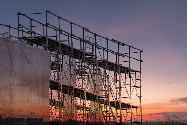 Bouwwerf met steigertoren en de bouw met zonsondergangachtergrond
