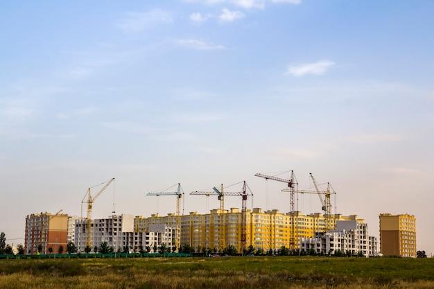 Bouwwerf van een nieuw flat hoog gebouw met torenkranen tegen blauwe hemel. woonwijkontwikkeling. onroerend goed project groei concept.