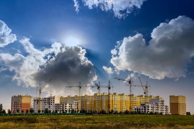 Bouwwerf van een nieuw flat hoog gebouw met torenkranen tegen blauwe hemel.
