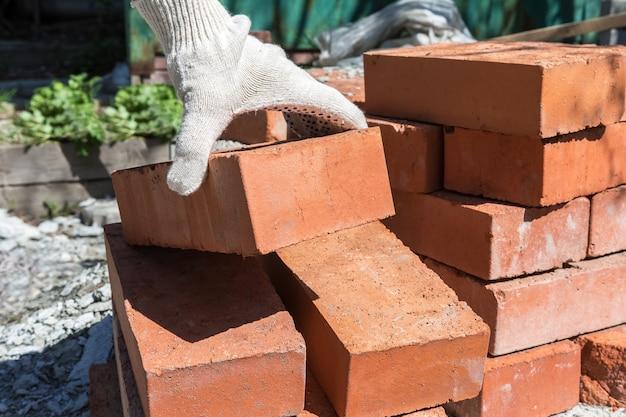 Bouwwerkzaamheden in de tuin een metselaar neemt een steen van een stapel om een schuurmuur te bouwen