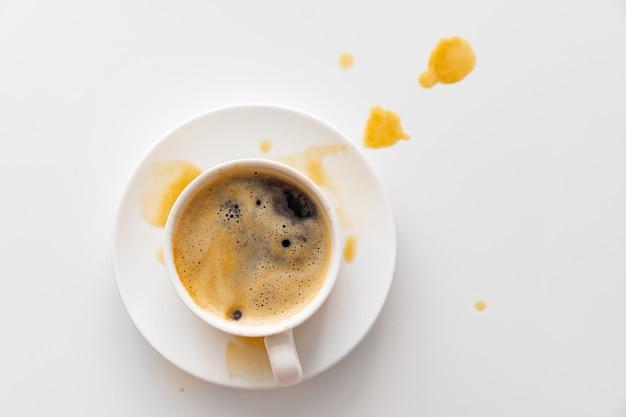 Boven bekijken. van kopje koffie spatten op de witte tafel. traditioneel ochtendontbijt.