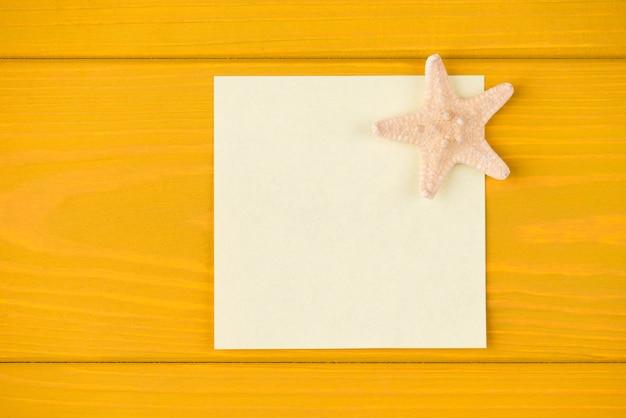 Boven boven bovenaanzicht close-up foto van lege notitie en zeester geïsoleerd op gele houten achtergrond met copyspace