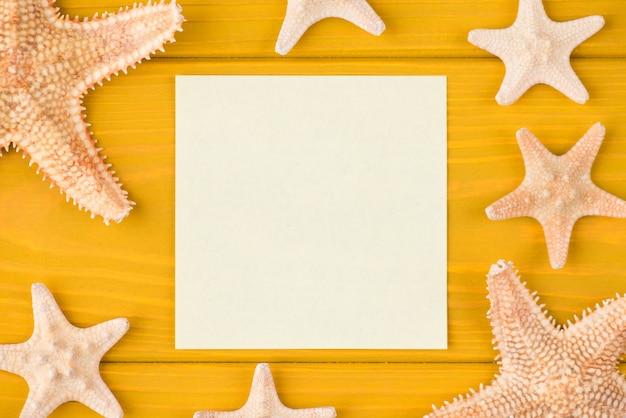 Boven boven bovenaanzicht close-up foto van lege sticker en zeester geïsoleerd op gele houten achtergrond met copyspace