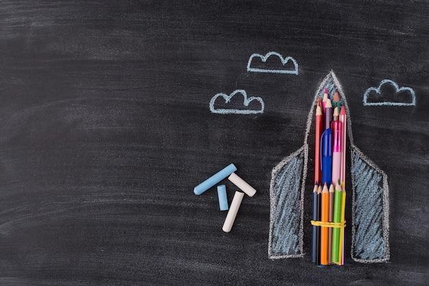Boven boven bovenaanzicht foto van getekende ruimteschip krijt en wolken geïsoleerd op schoolbord achtergrond met copyspace