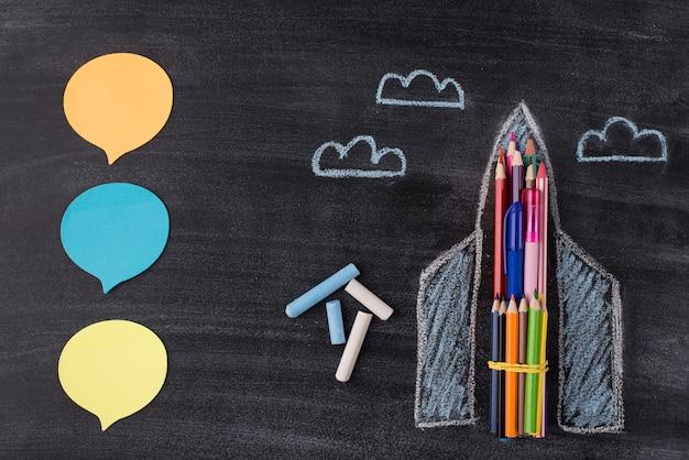 Boven boven bovenaanzicht foto van getekende ruimteschip krijt notities en wolken geïsoleerd op schoolbord achtergrond met copyspace