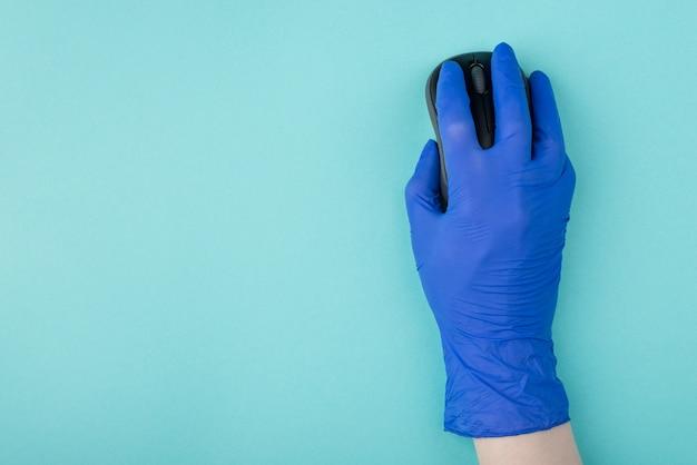 Boven boven bovenaanzicht foto van hand in handschoen met draadloze muis om te zoeken naar noodzakelijke informatie over coronavirus geïsoleerd op turkooizen achtergrond