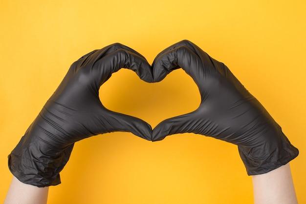Boven boven bovenaanzicht foto van vrouw handen in zwarte handschoenen maken hart geïsoleerd op gele felle kleur achtergrond