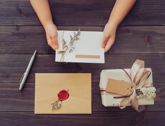 Boven de hand meisje houd kaart en ambachtelijke geschenkdoos op houten tafel achtergrond