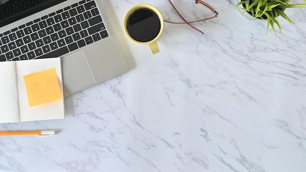 Boven de opnametafel, bureau marmeren tafel met laptop, notebookpapier, potlood, glazen en koffiekopje.