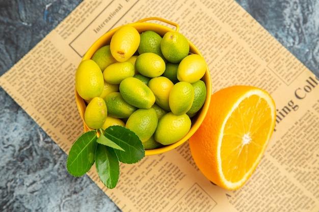 Boven dichtbij zicht van citrusvruchten in een mand op krant op grijze achtergrond