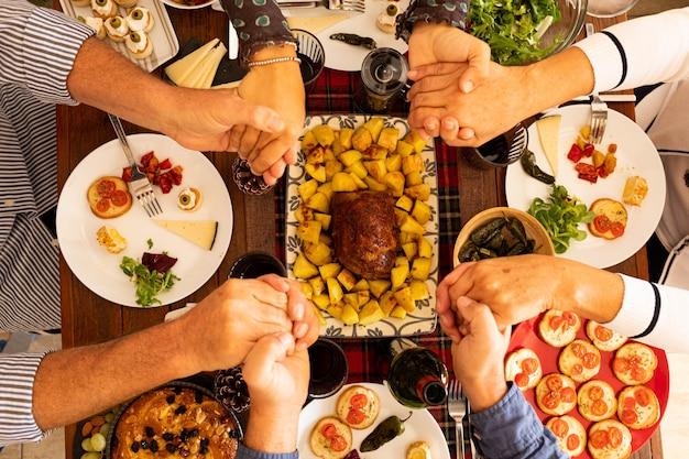 Boven- en bovenaanzicht op een grote tafel en mensen die eten en bidden en danken bij god of iemand over hun eten