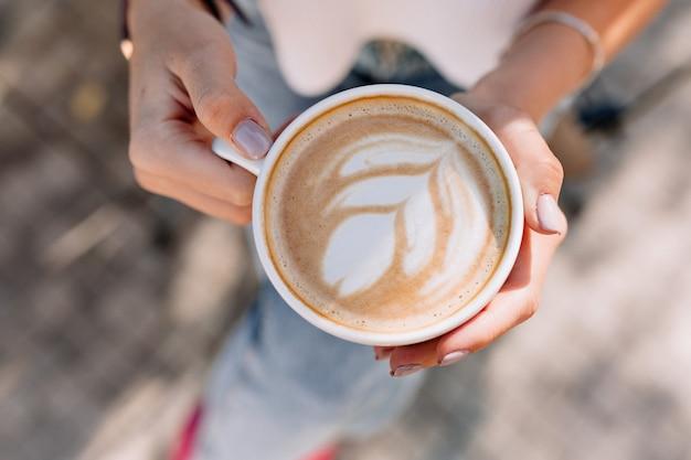 Boven frame van een kopje koffie in de hand van de vrouw buiten in de zomer zonnige straat