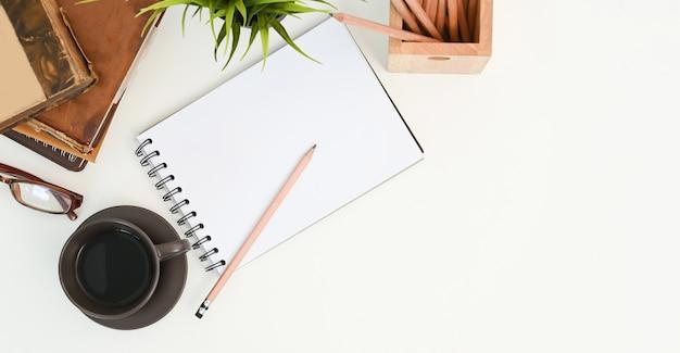 Boven geschoten bureauwerkruimte met notitieboek, kantoorbenodigdheden en koffiekop op witte lijst.