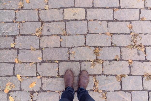 Boven geschoten van de mens die zich op baksteen gevormde vloeren bevindt