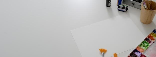 Boven geschoten van de werkruimte van de kunstenaar met schetspapier, kleurenpalet, tekengereedschappen en kopieerruimte