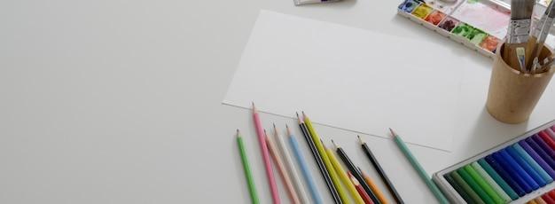 Boven geschoten van de werkruimte van de kunstenaar met schetspapier, oliepastels, tekengereedschappen en kopieerruimte