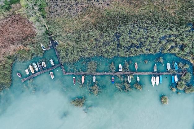Boven geschoten van een klein dok aan de kust met geparkeerde vissersboten