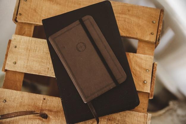 Boven geschoten van een notitieboekje op de bijbel op een houten doos