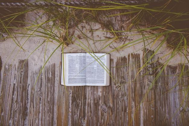 Boven geschoten van een open bijbel op een houten weg dichtbij een zandige kust en installaties