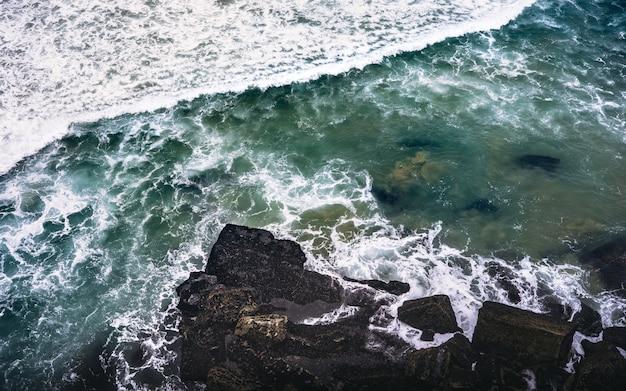 Boven geschoten van een rotsachtige kust dichtbij een watermassa met rotsen die op de rotsen bespatten