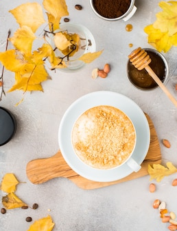 Boven geschoten van koffie met noten in een witte keramische beker op een tafel met een kom met honing en beer