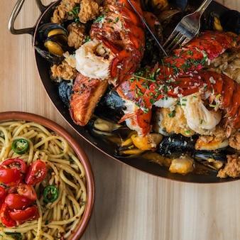 Boven geschoten van pasta in de buurt van een pan van gebakken kreeft en vlees met oesters op een houten oppervlak