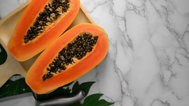 Boven geschoten van plak van zoete papaja op houten dienblad en exemplaarruimte