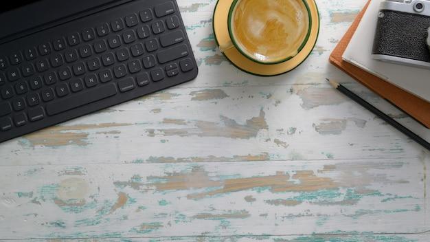 Boven geschoten van rustieke werkplek met tablet, camera, kantoorbenodigdheden, koffiekopje en kopie ruimte