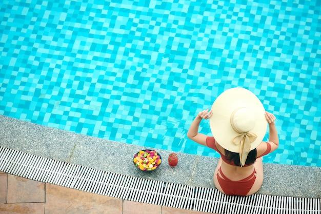 Boven het beeld van een vrouw die op de rand van het zwembad zit en de zomerhoed aanpast