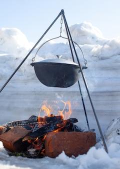 Boven het vuur hangt een pot om voedsel in te koken. aan een haak op een statief komt er stoom uit de pan. winterkamperen buiten koken