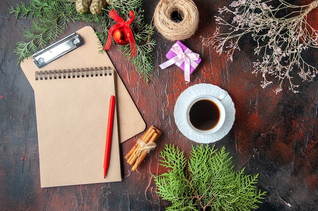 Boven het zicht op een kopje zwarte thee dennentakken, kaneellimoenen cadeau en notitieboekje op donkere achtergrond